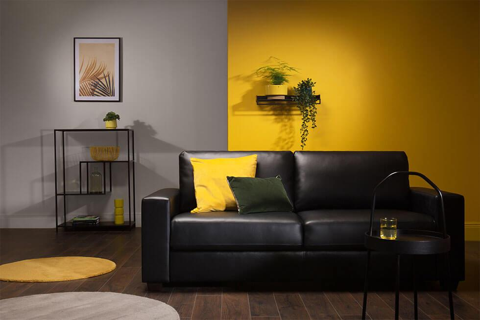 Yellow and grey modern living room with a black leather sofa