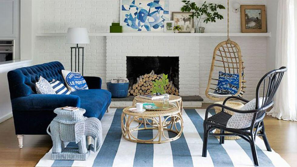 A blue living room furnished with a dark blue velvet sofa and neutral accessories.