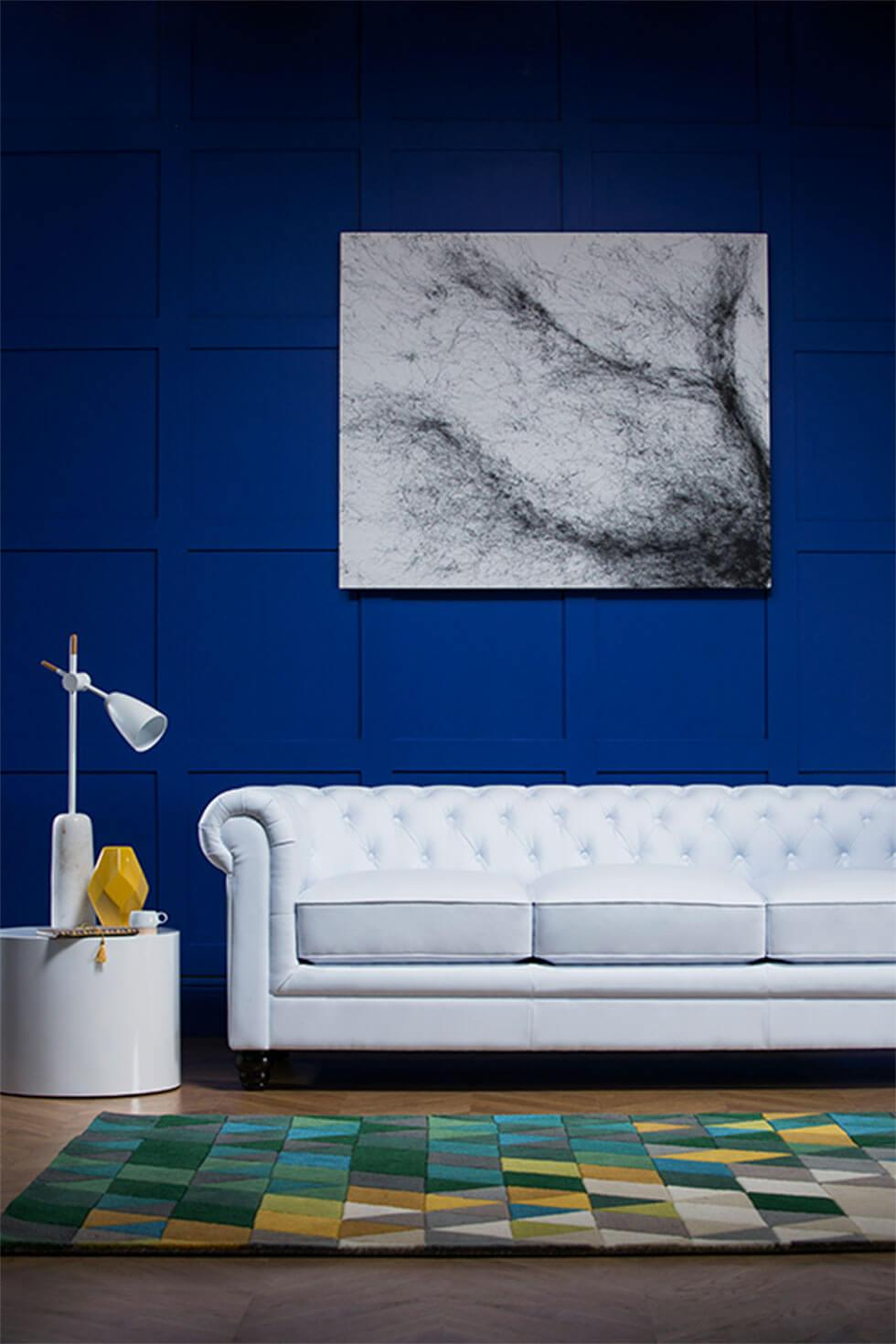 A white leather Chesterfield sofa in a living room with bold blue walls.
