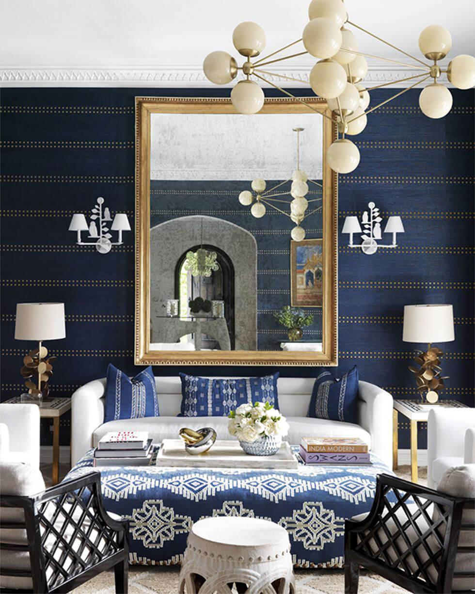 A dark blue living room with a modern chandelier and white sofa.