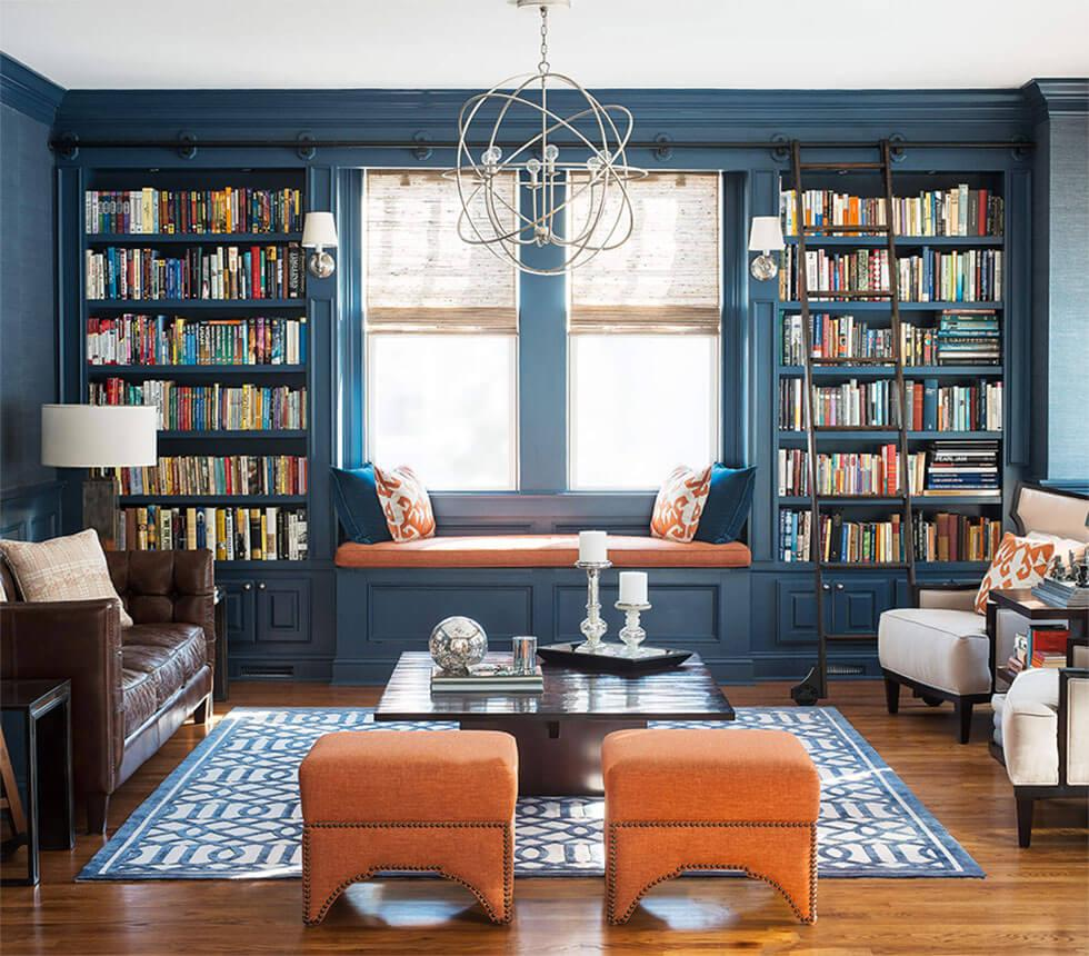 A blue living room with a home library and pops of orange.
