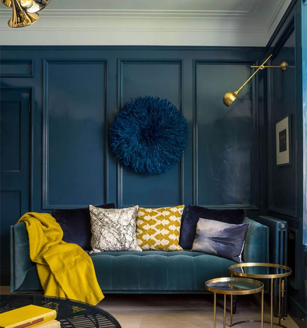 Dark blue living room walls with contrasting yellow cushions and accents.