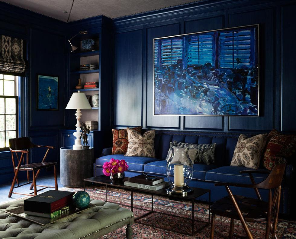 A living room with dark blue lacquer paint and dark blue sofa.