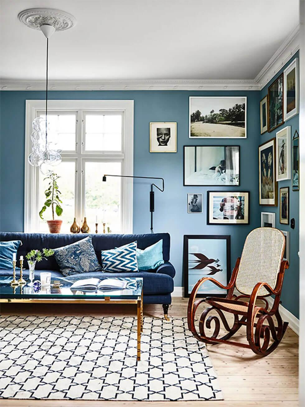 A blue living room with a gallery wall and a blue sofa.