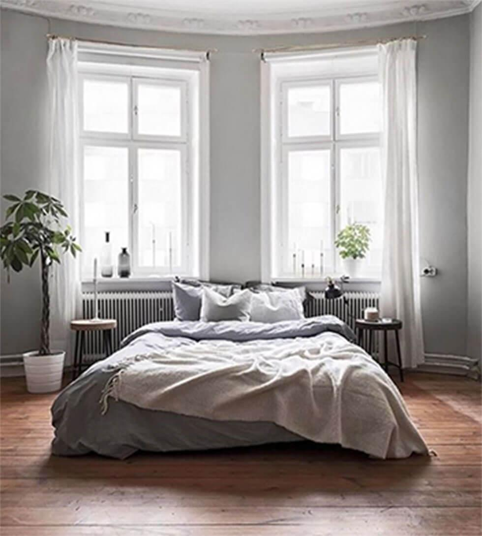 Grey bed in a grey bedroom with large windows.