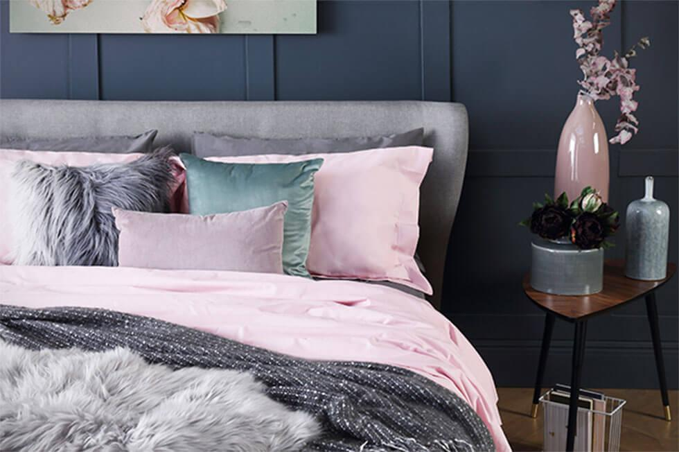 Grey upholstered bed, pink pillows in a dark grey bedroom.