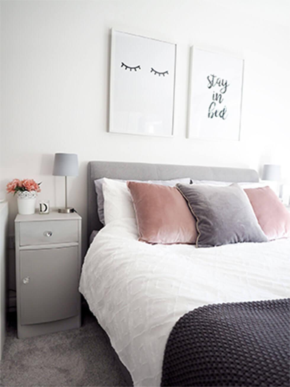 Light grey bed with dusty pink pillows in a light grey bedroom.