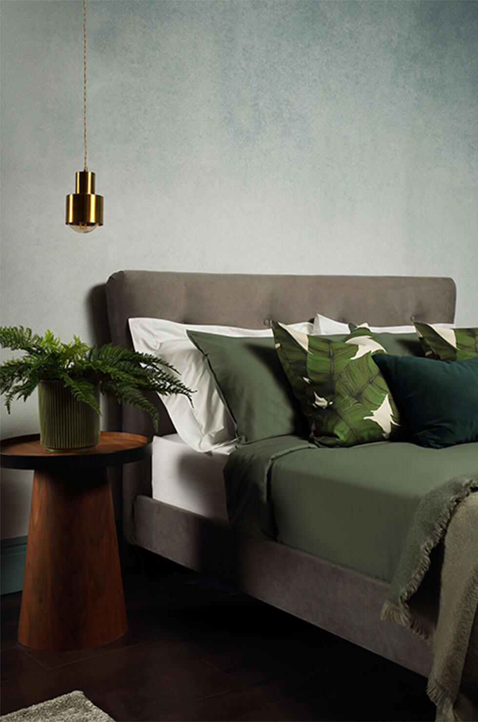 Grey velvet bed, green pillows in a grey bedroom.