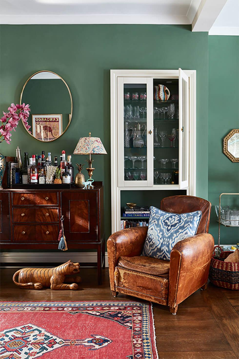 Classic olive green living room with warm brown leather armchair, dark wood chest of drawers and a printed rug