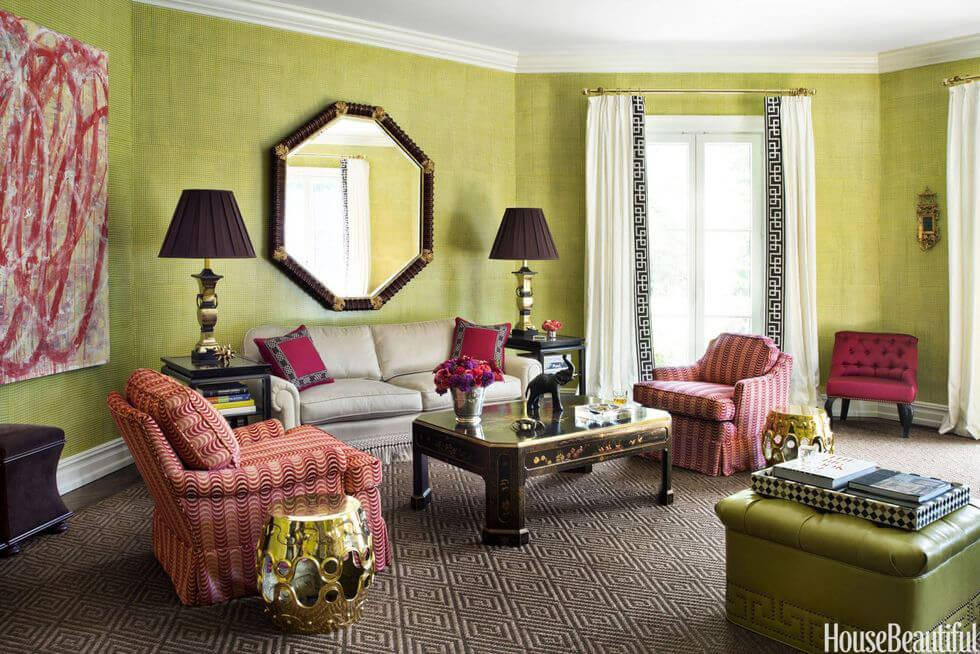 Light green living room with large mirror, brass accents and red armchairs