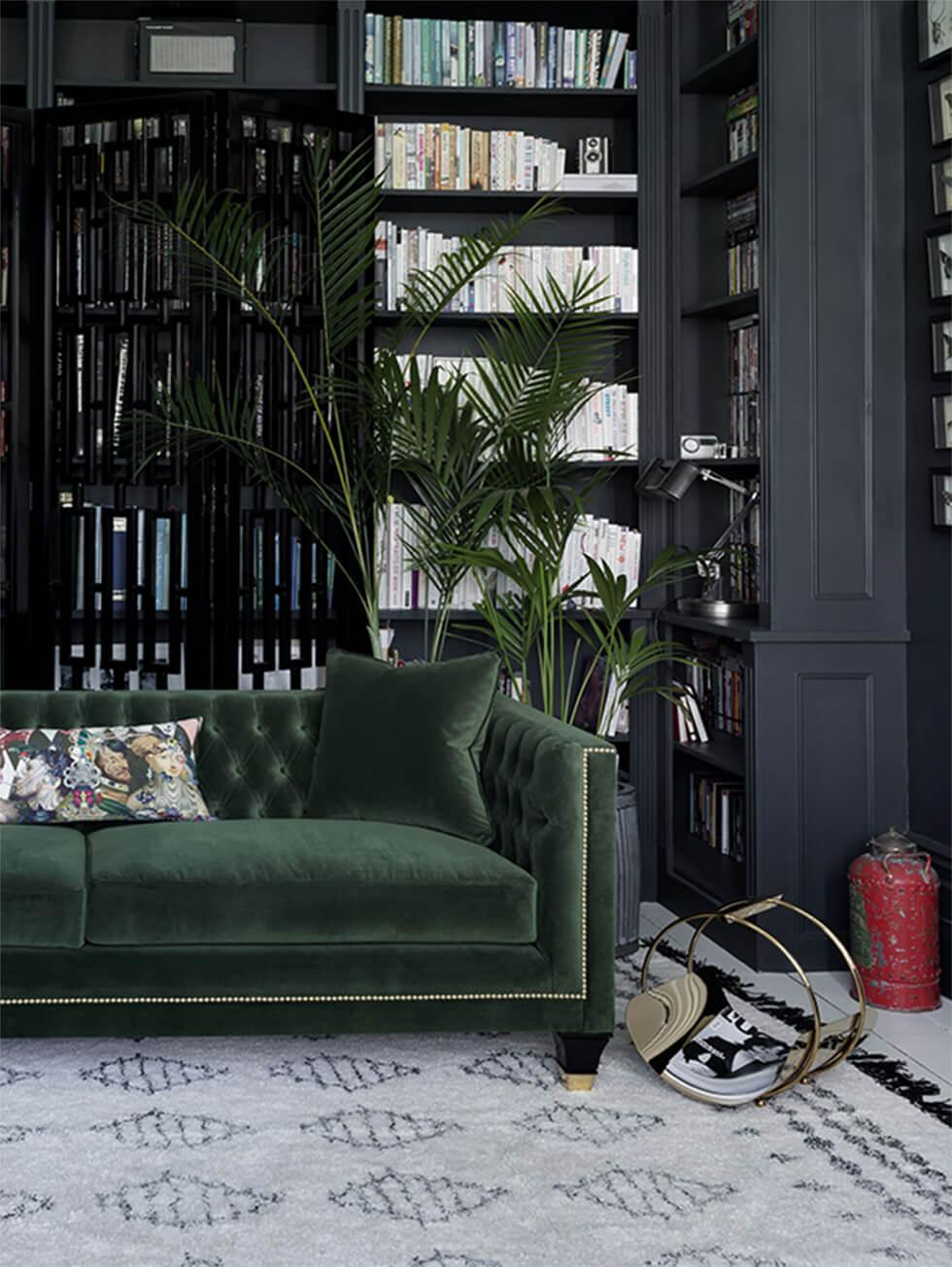 Moody, elegant dark green living room with green velvet Chesterfield sofa and grey walls