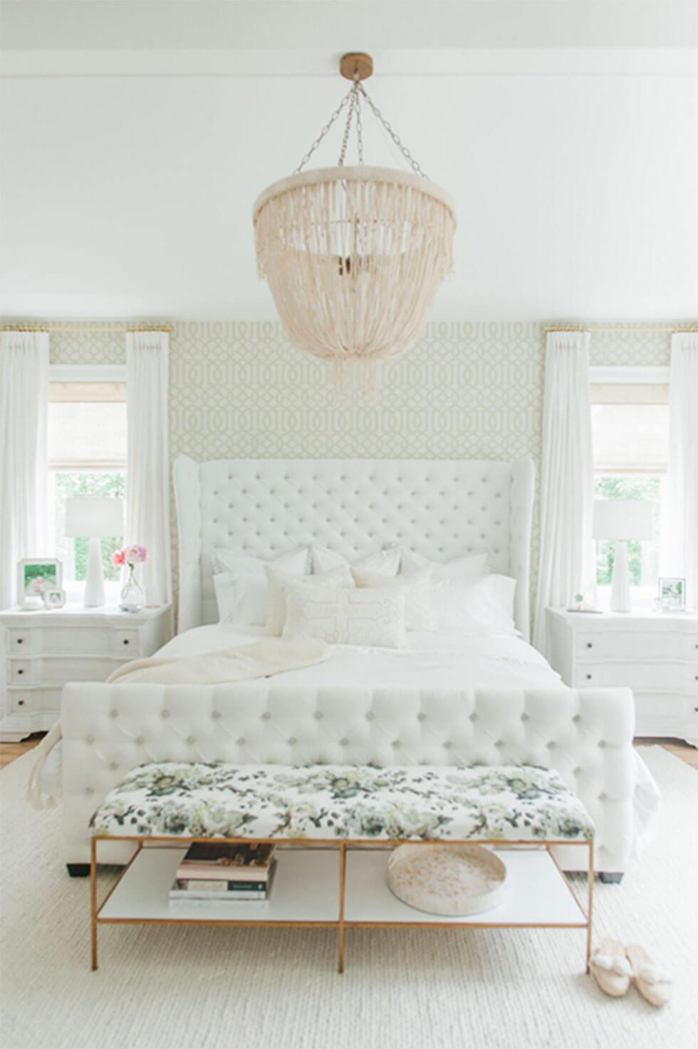 All-white bedroom with tufted headboard and beaded chandelier.