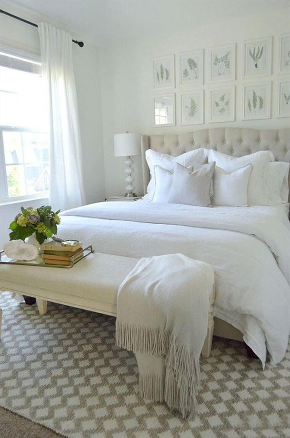 All-white bedroom with tufted headboard, linen bedding and upholstered bench.