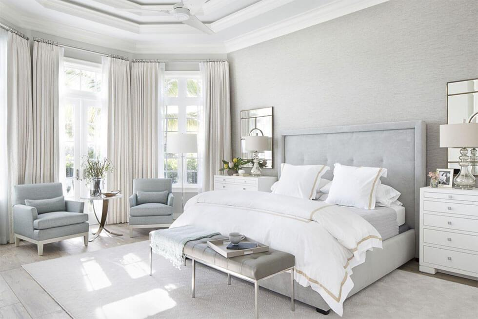 White bedroom with grey bed and armchairs.