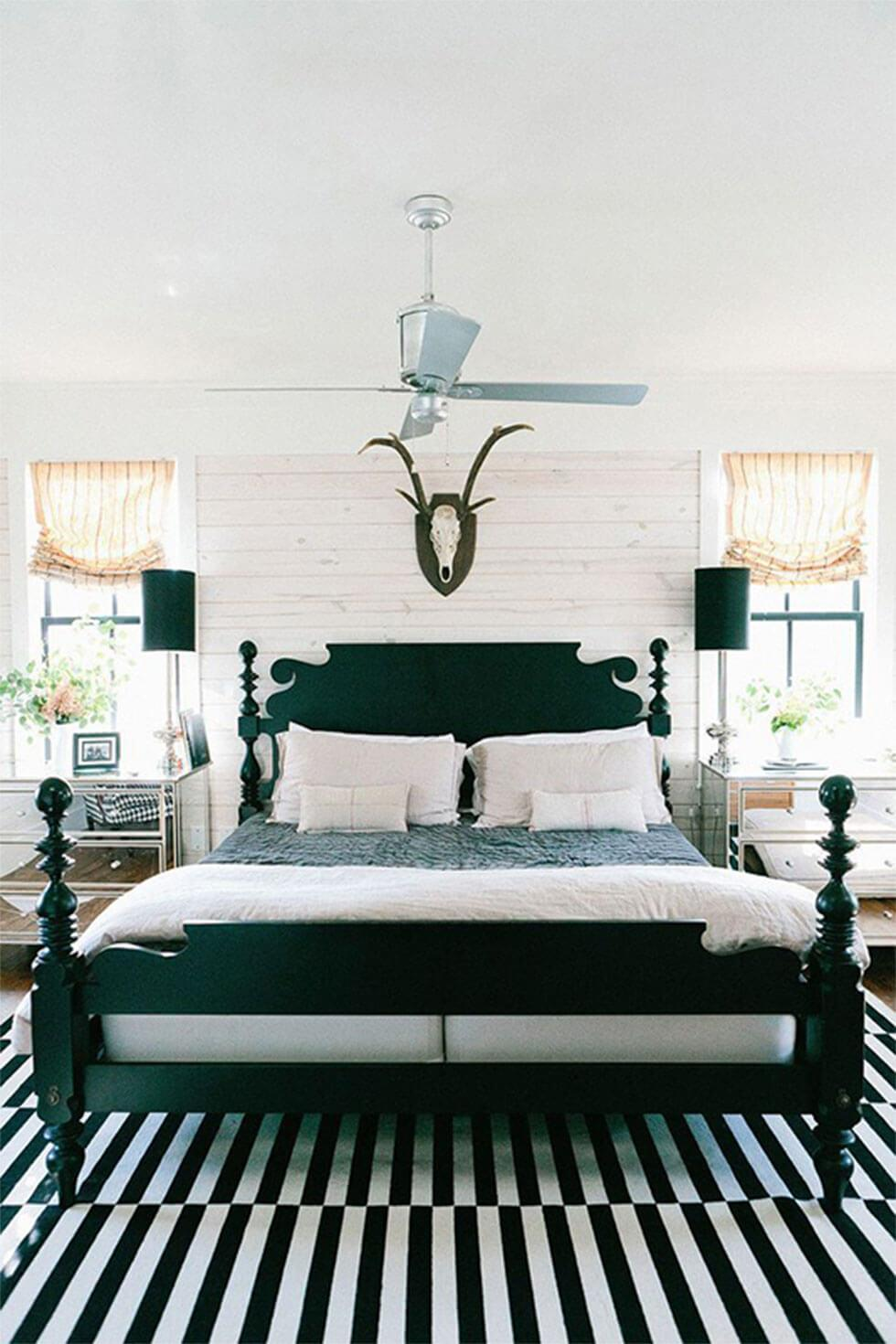 Black and white bedroom with black headboard and striped rug.