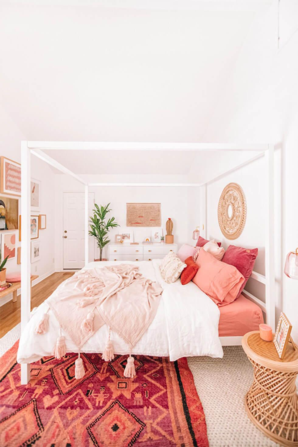 White bedroom with pink decor and canopy bed.