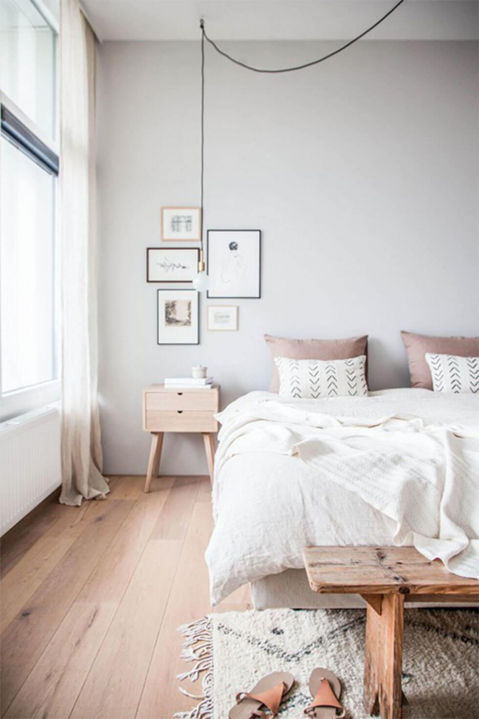 White bedroom in Scandinavian style with light wood furniture.