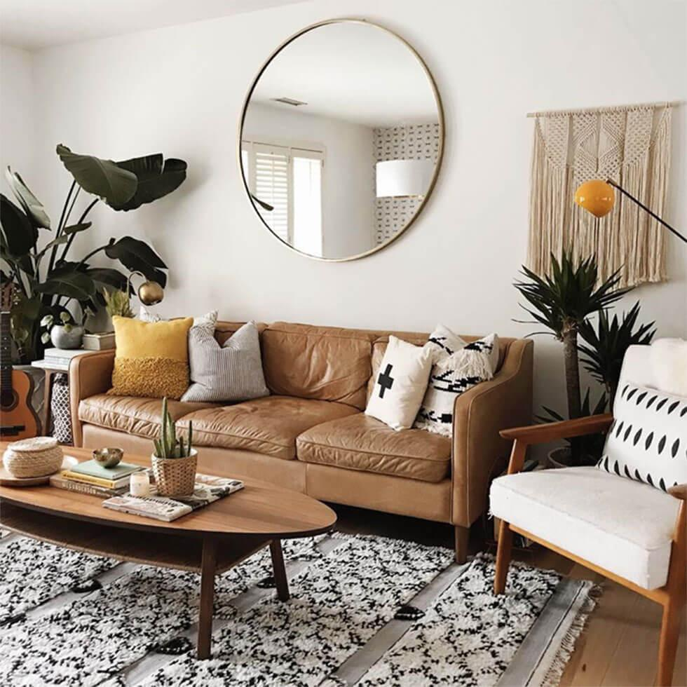 A round mirror above the sofa in the living room