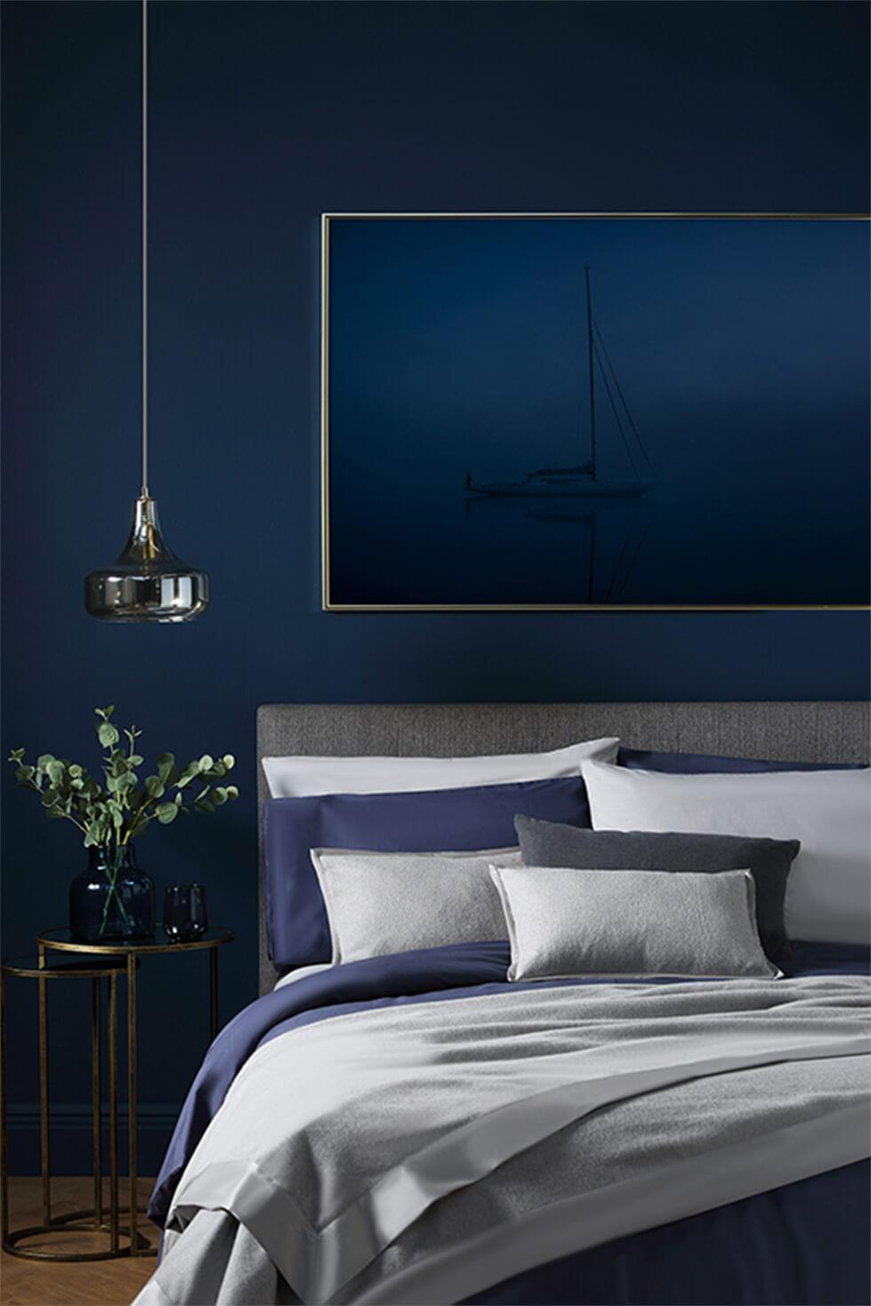 Navy bedroom with grey and blue bedding and gold accents