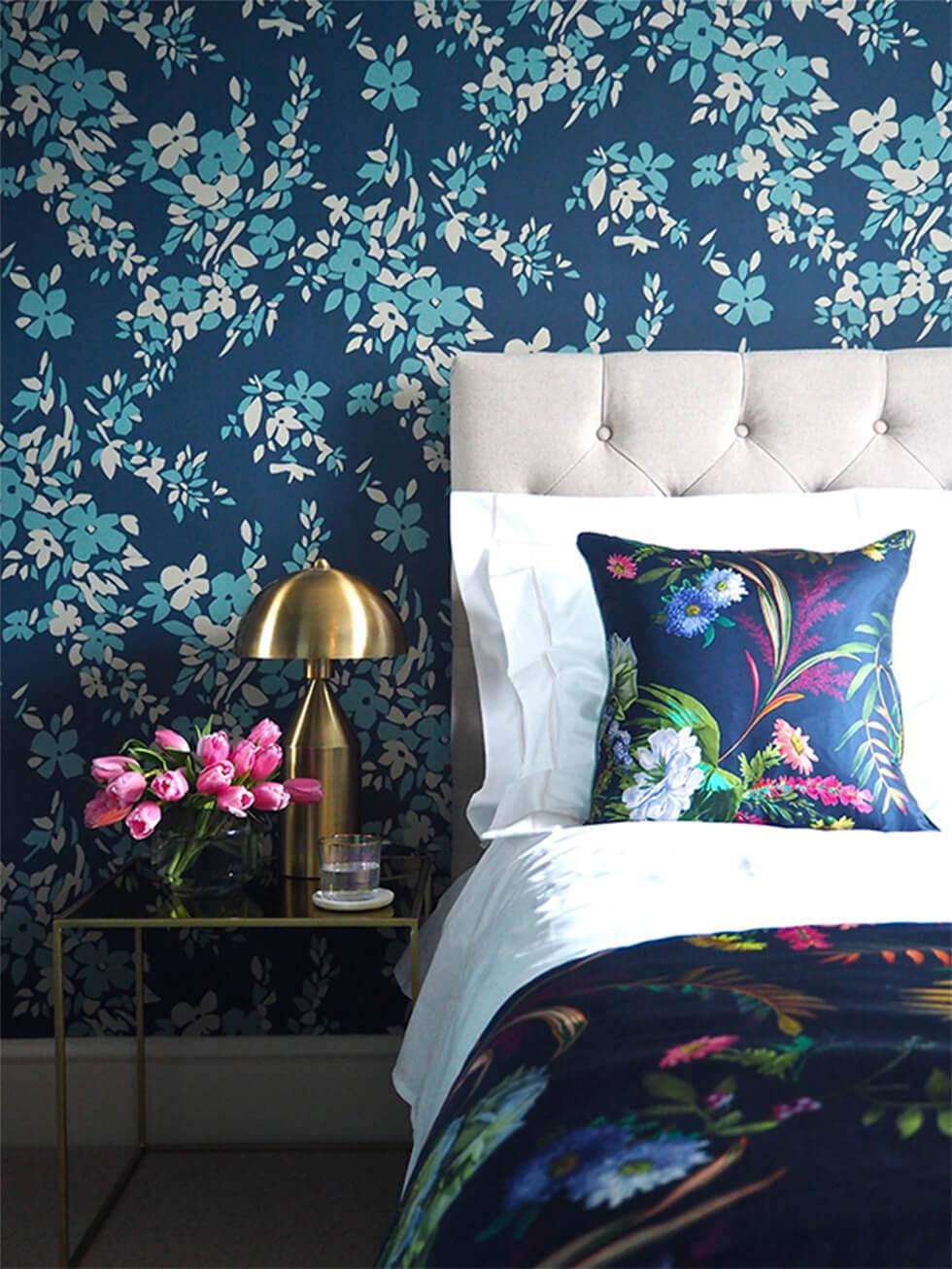 Maximalist blue bedroom with floral wallpaper and colourful bed linen