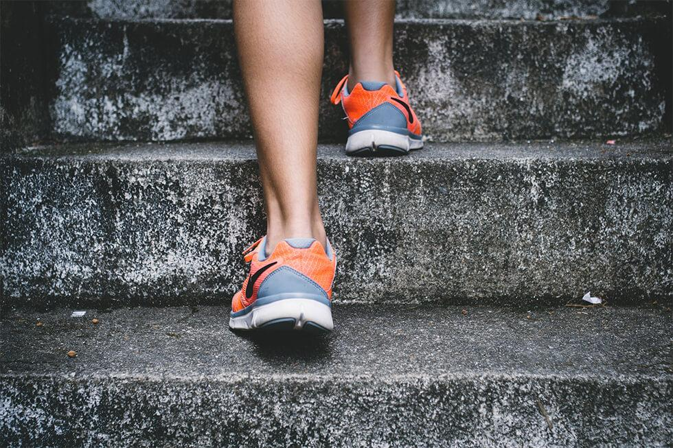 person wearing orange running shoes on stairs.