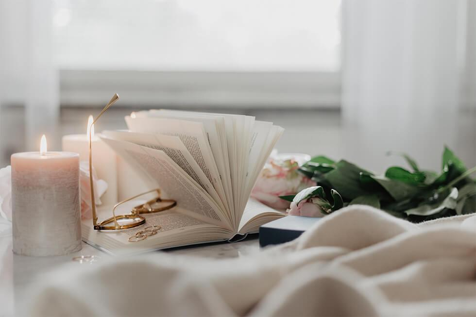 Candles, plants, and a book in a wellness inspired room.