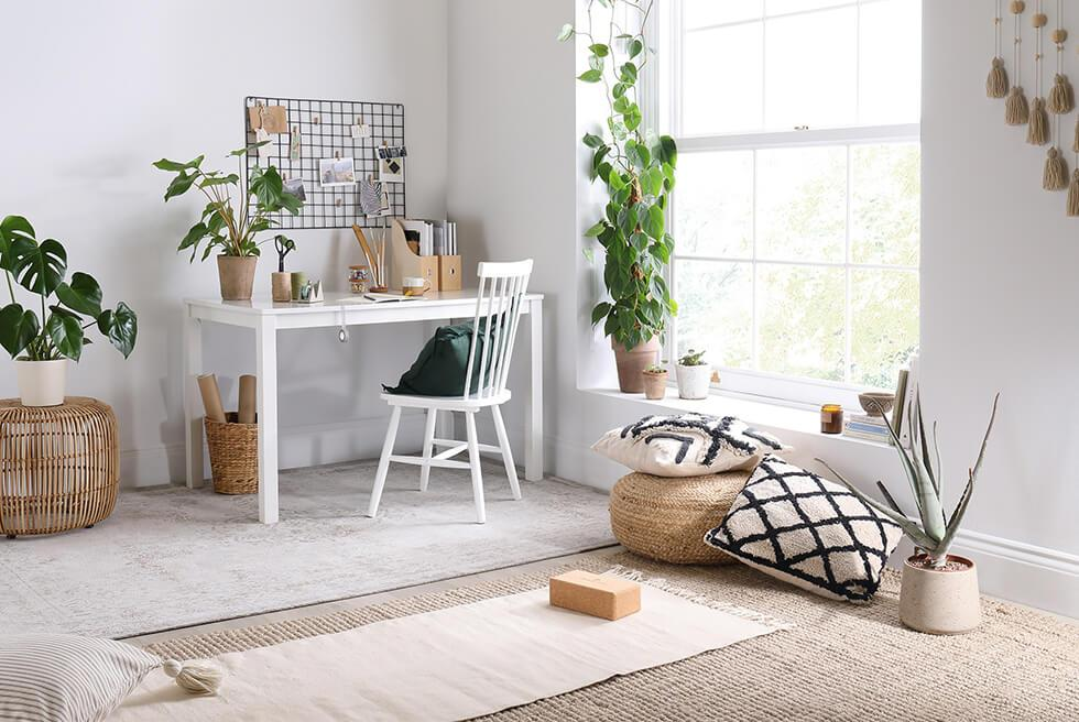 White wooden table and yoga corner in a mindful living interior.