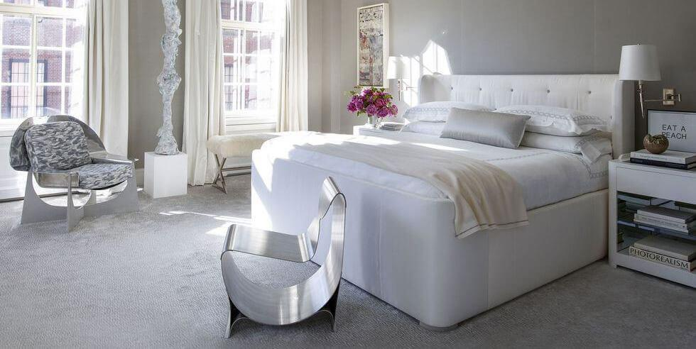 Neutral grey bedroom with statement silver chairs