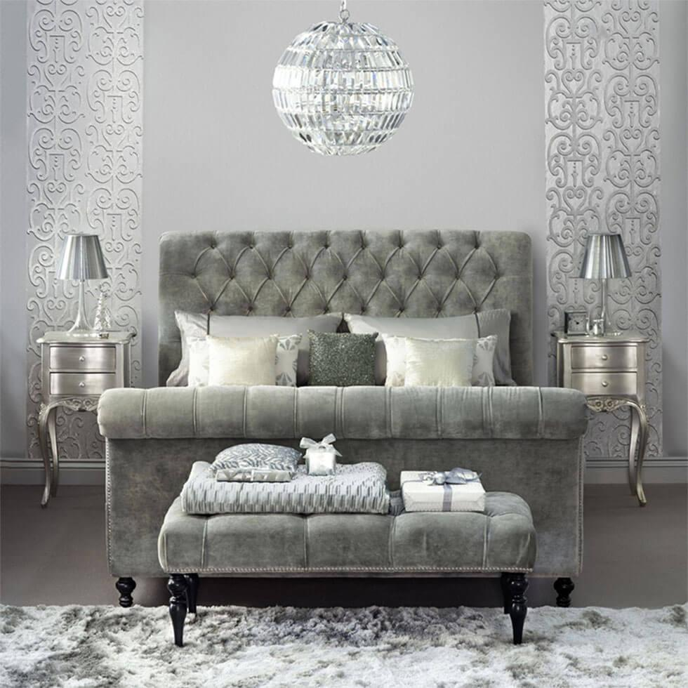 Grey bedroom with a silver bed with a tufted headboard and a disco chandelier