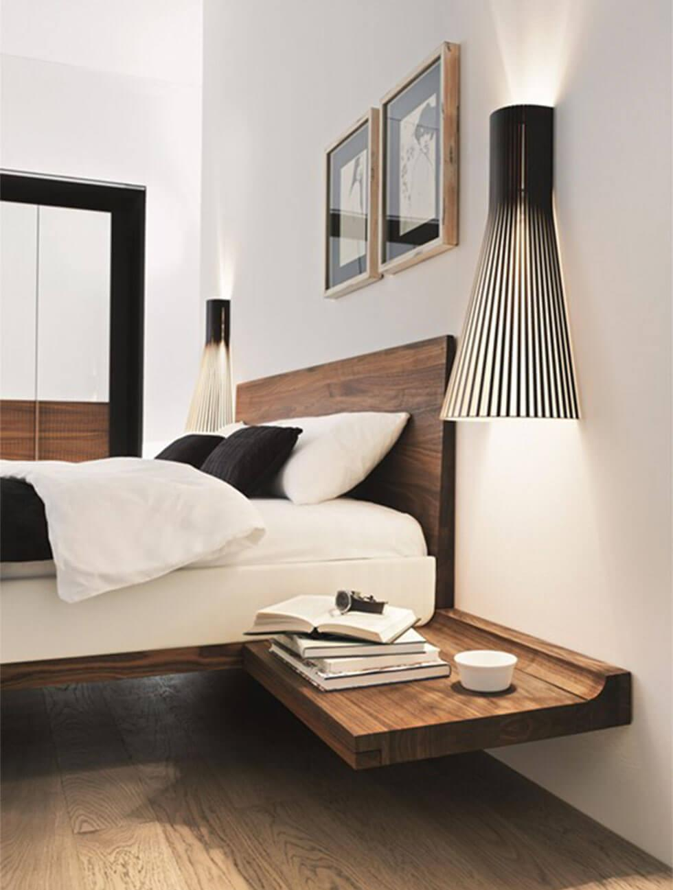 Minimal bedroom with floating bed and modern wall lamps