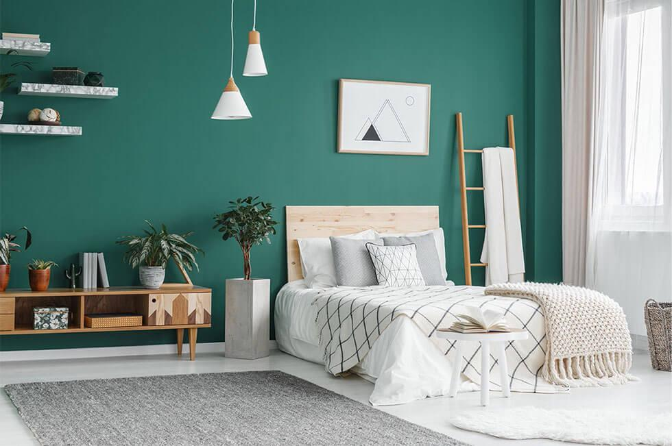 Scandinavian style bedroom with a green wall