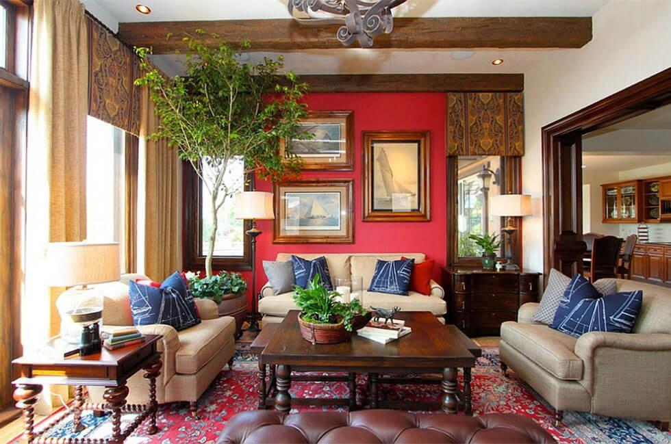 A red and blue living room with blue pillows, neutral sofas and a large indoor plant