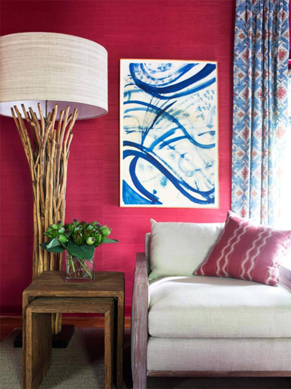 Red living room with a cream sofa, blue and white art, and a large lamp