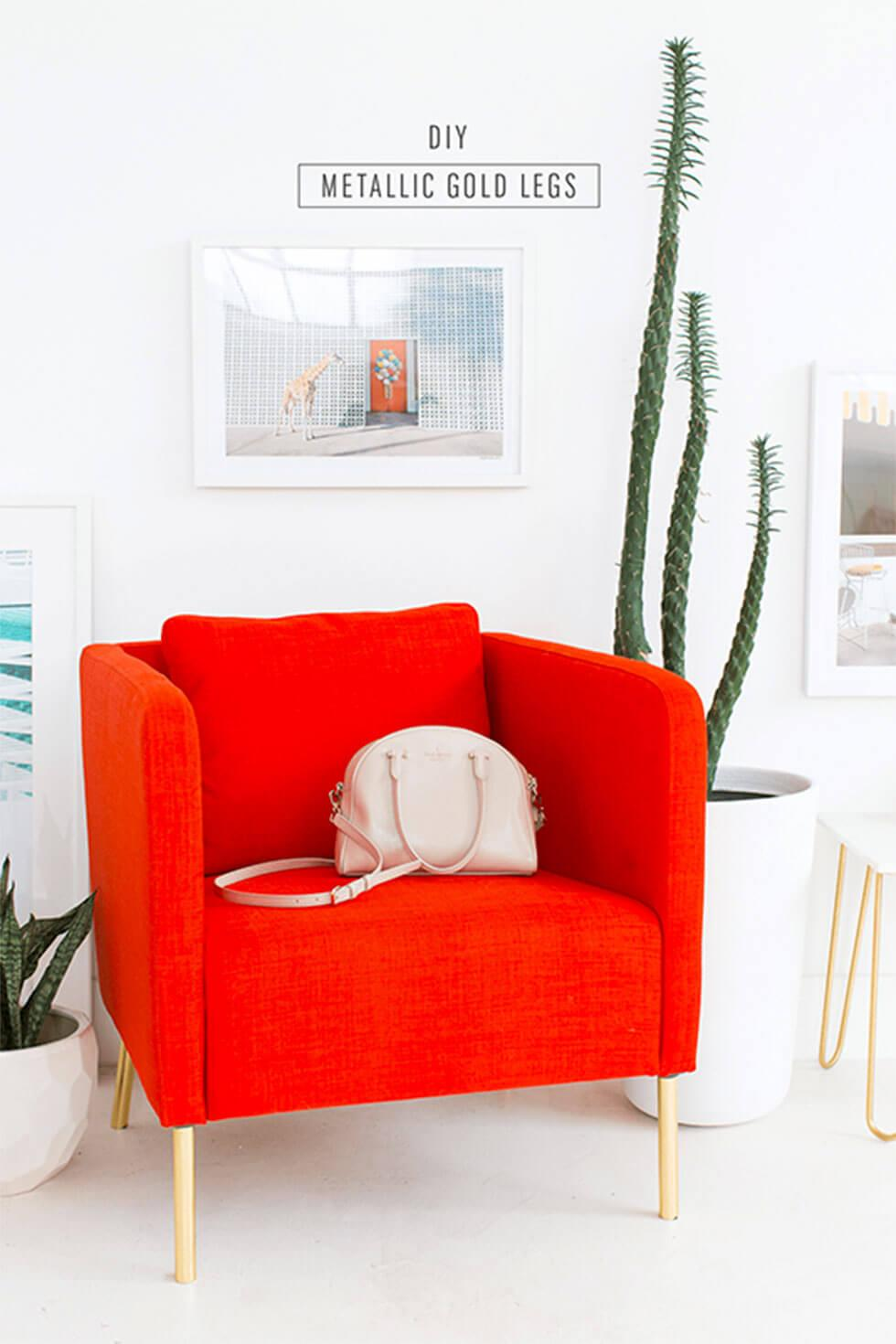 Bright red orange armchair with gold legs in a white room
