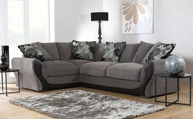 Grey corner sofa with a light grey rug against a brightly lit interior.