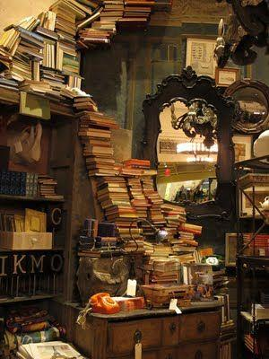 A desk and shelf stacked with books.