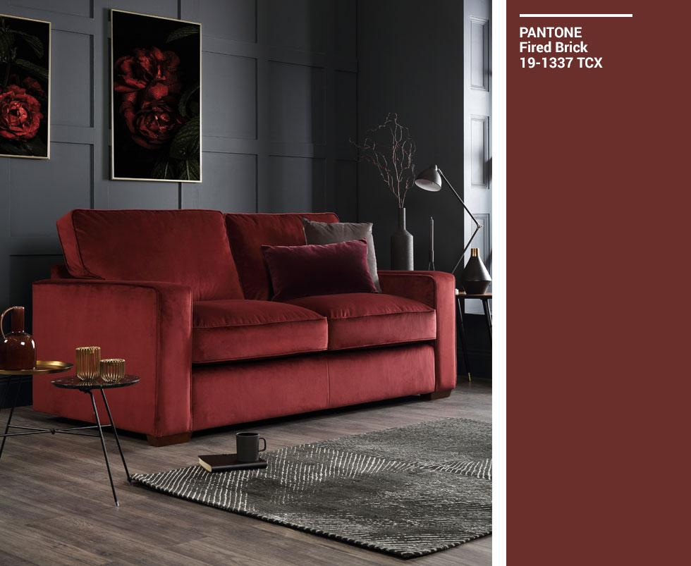 Deep red sofa in a dark grey living room, with a Pantone swatch.