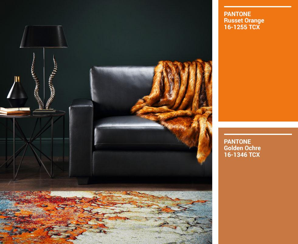 Black leather sofa accented with an ochre fur throw, with matching Pantone swatches.