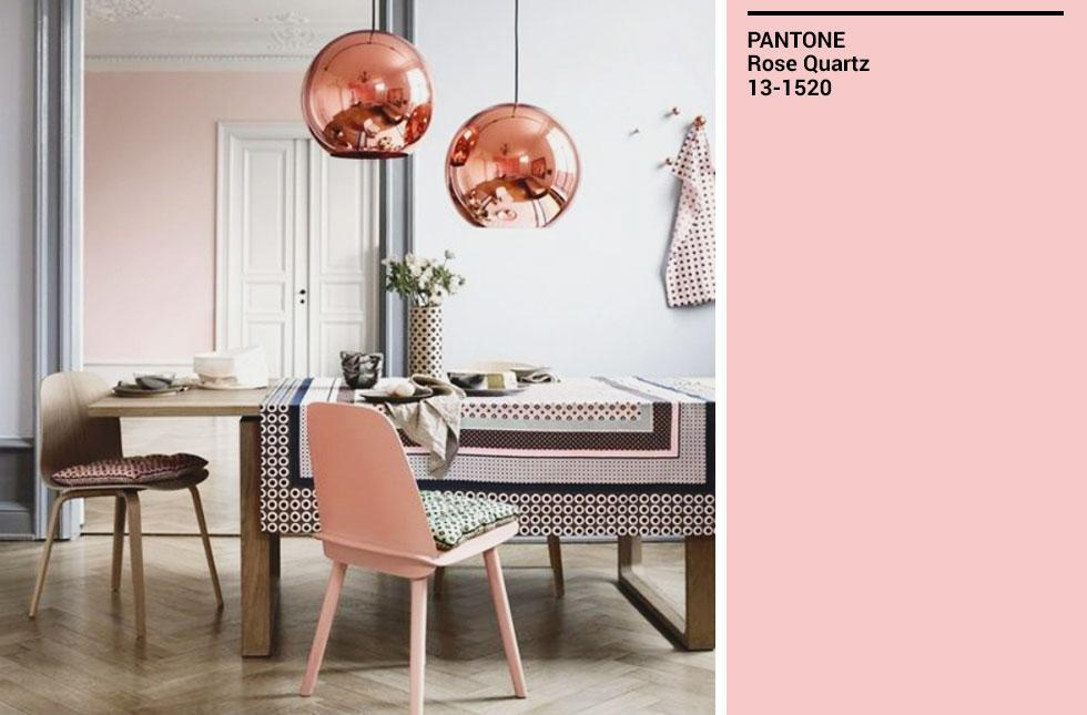 A dining room with a pink chair, wooden table, and rose gold lamps.