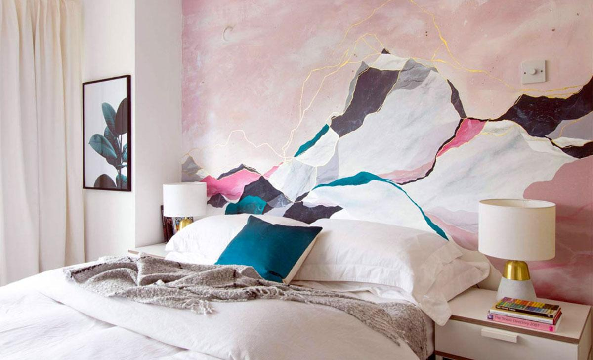 A pale pink bedroom with contrasting teal pillows.