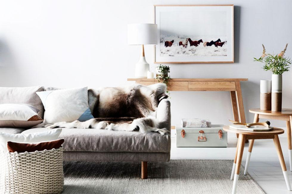 A living room in neutral tones with a fur throw