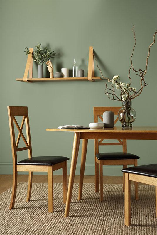 Wooden dining set with leather strap shelf against a sage walll