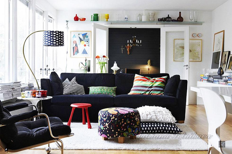 Living room with a monochrome theme and large black sofa.