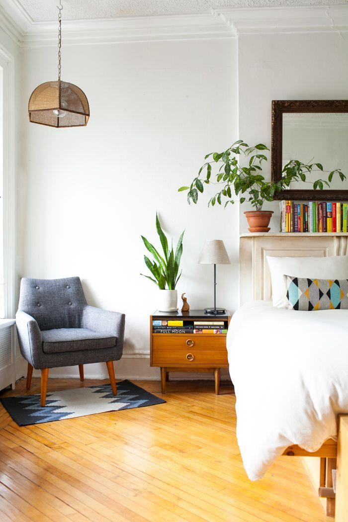 A light and airy bedroom with wooden floors, white bedding, a grey armchair and plants.