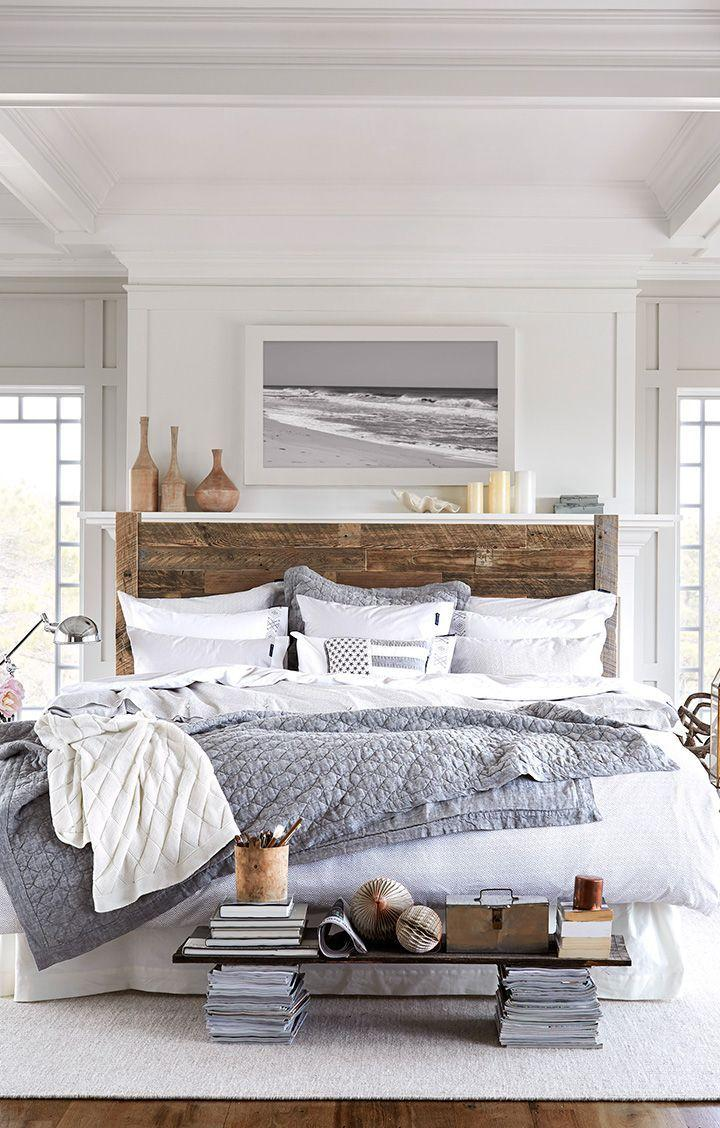 An airy, white bedroom with a large wooden bed, and grey blankets.