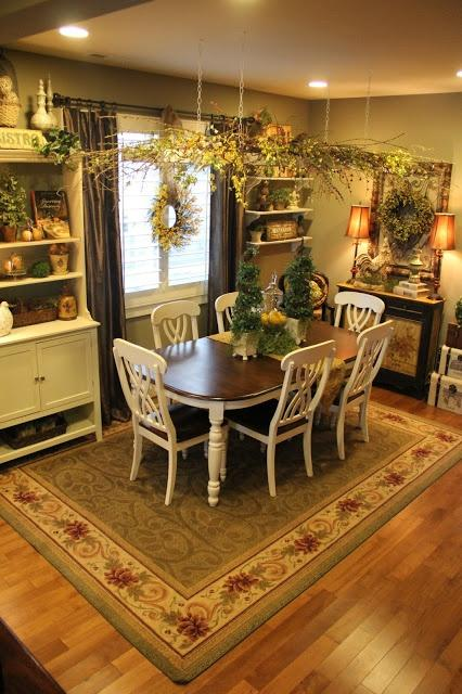A dining room with a wooden table with white legs, and matching white chairs, with a carpet and lots of plants.