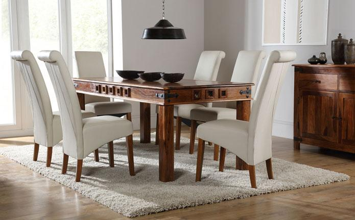 Solid wooden table with white modern leather chairs.
