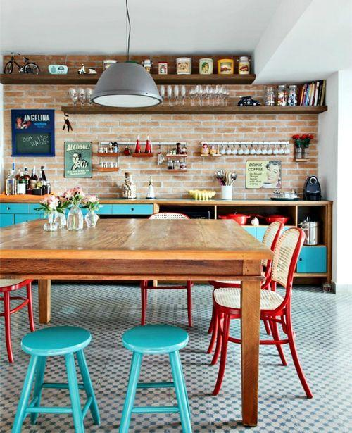A dining room and kitchen with a large wooden table, tiled floors, brick walls and colourful chairs.