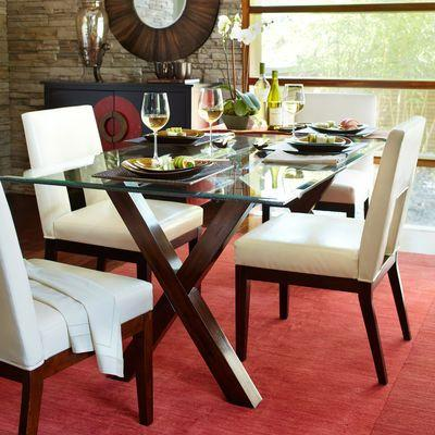 A glass dining table, with wooden legs, white chairs, on a red carpet.