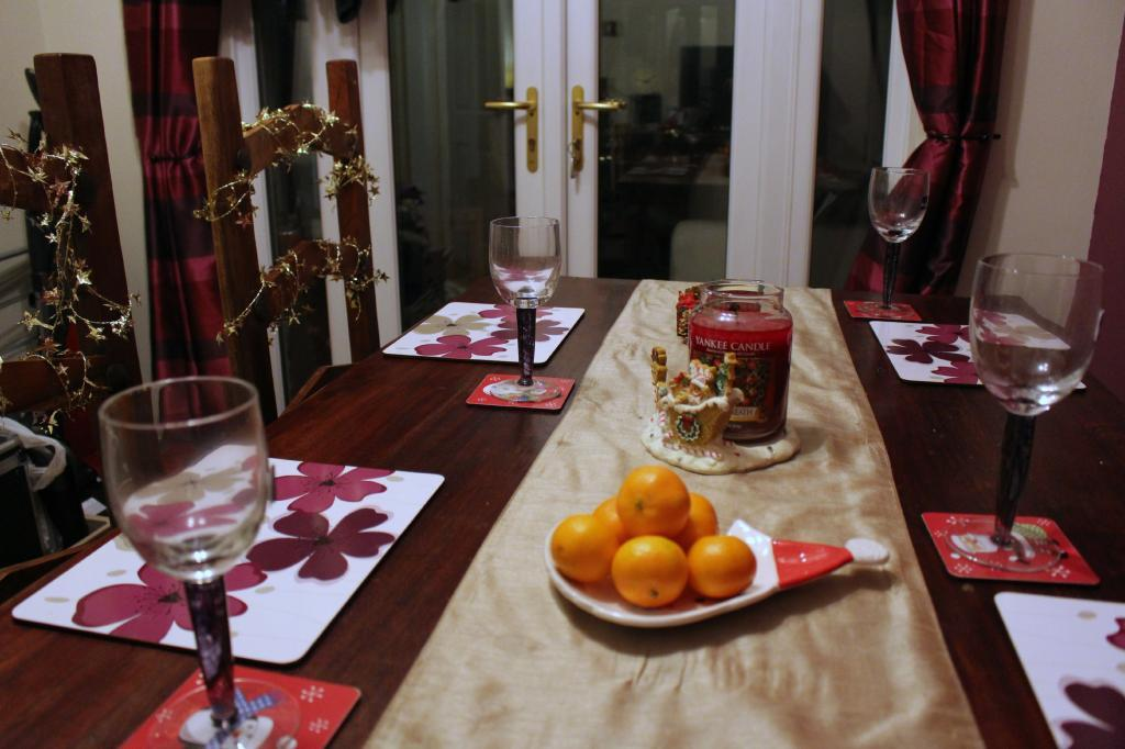 Wooden dining table set for a meal, with a plate of oranges.